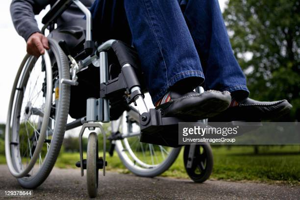 Man in wheelchair on path in park, low section
