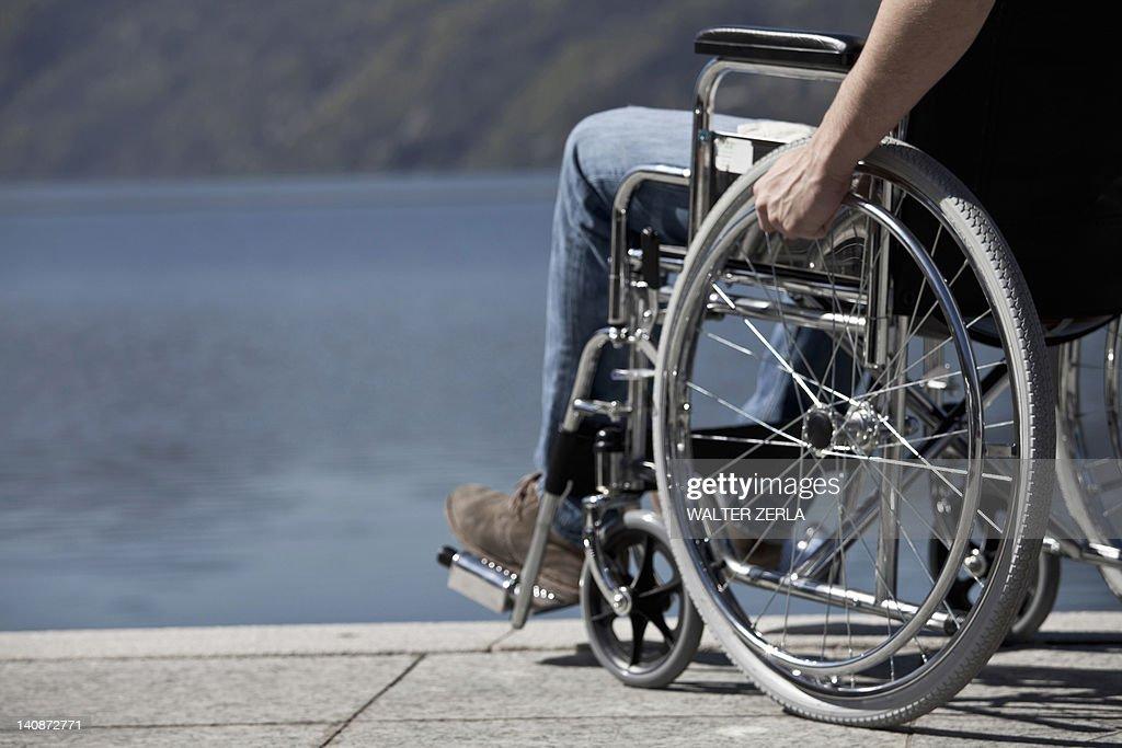 Man in wheelchair sitting by water : Foto de stock