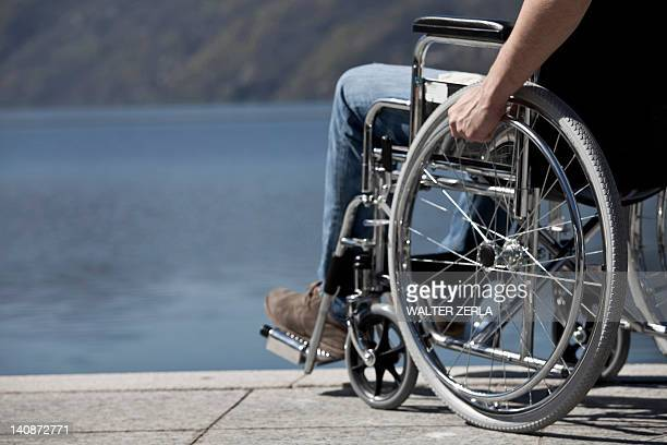 man in wheelchair sitting by water - paraplegic stock photos and pictures