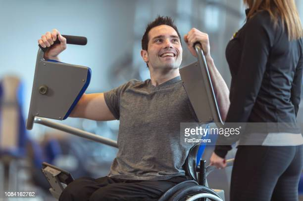 man in wheelchair training at a gym - spinal cord injury stock photos and pictures