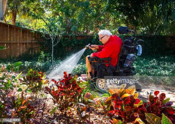 Man In Wheelchair Watering Front Yard House Garden
