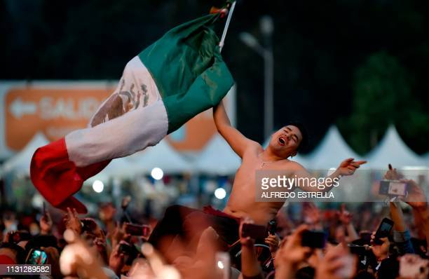 A man in wheelchair waves a Mexican flag as he enjoys the performance of Mexican rock band El Tri while he is lifted above the crowd during the...