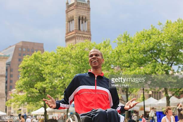 Man in wheelchair who had Spinal Meningitis at a city Farmer's Market
