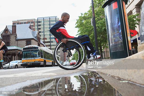 man in wheelchair who had spinal meningitis going over a curb - curb stock pictures, royalty-free photos & images