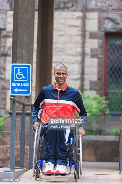 Man in wheelchair who had Spinal Meningitis using a ramp