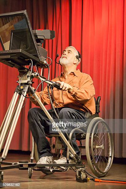 man in wheelchair with muscular dystrophy using a tv camera and a teleprompter in studio - teleprompter stock pictures, royalty-free photos & images