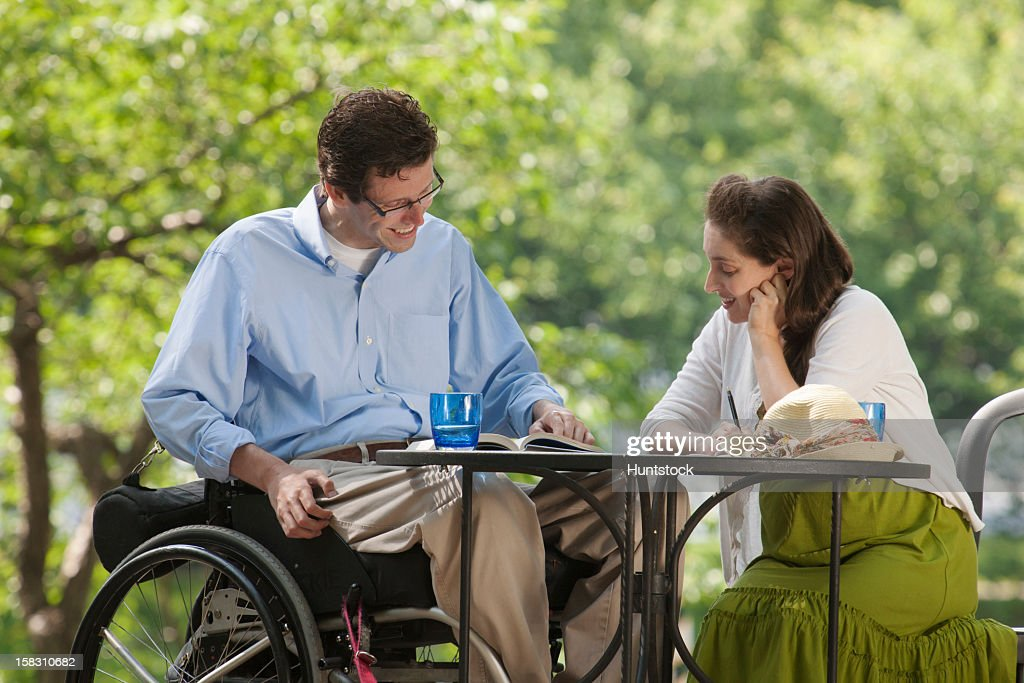 Man in wheelchair with spinal cord injury reading a book at cafe with his pregnant wife : Stock Photo