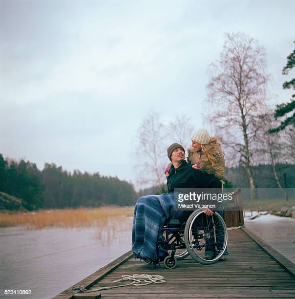 man in wheelchair with woman on dock - paraplegic woman stock photos and pictures