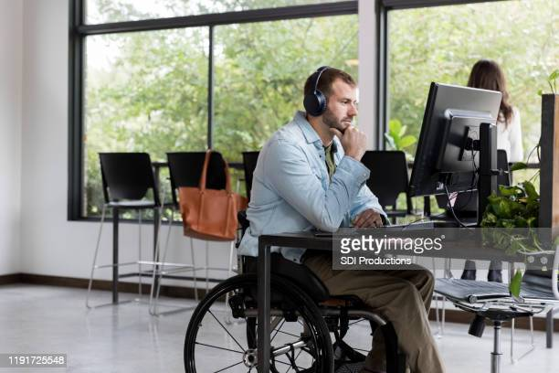 man in wheelchair working in it support - financial analyst stock pictures, royalty-free photos & images