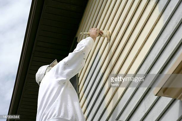 Man in white coveralls painting the outside of a house