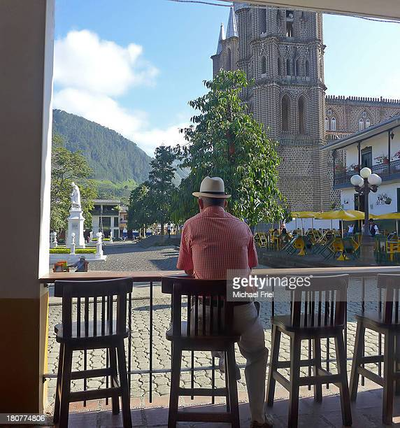 CONTENT] man in white hat contemplates the main square in Jardin Colombia as he sits drinking coffee
