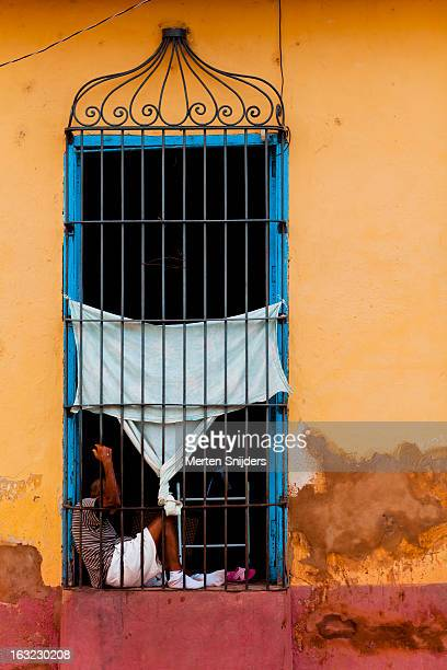 man in window frame leaning on fence - merten snijders photos et images de collection