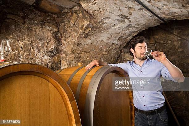 Man in wine cellar tasting wine