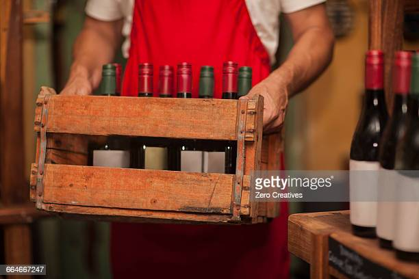 Man in wine shop carrying wooden crate of wine
