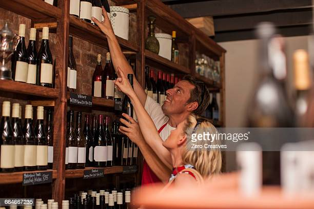 Man in wine shop helping customer reach wine bottle on top shelf