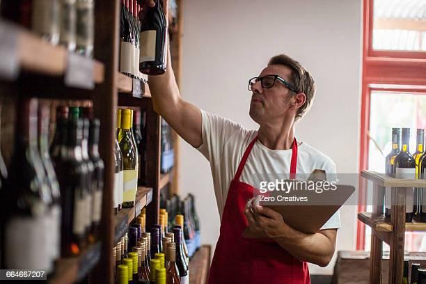 Man in wine shop stock taking bottles of wine
