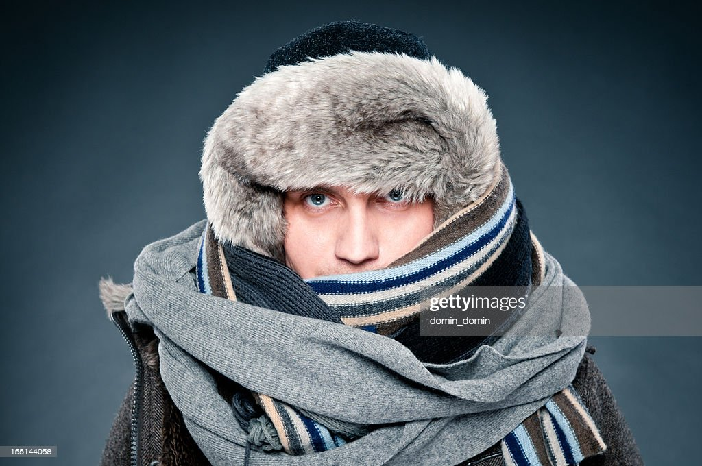 Man in winter clothes is tightly bundled up, cap, scarves : Stock Photo
