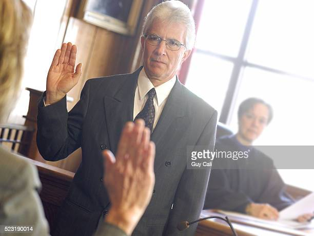 man in witness box swearing oath - witness stock pictures, royalty-free photos & images