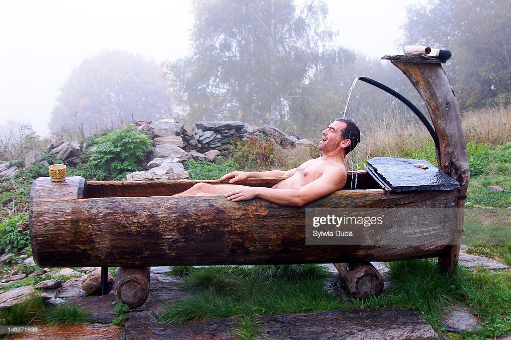 Man in wooden bathtub : Stock Photo