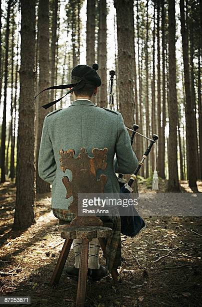 Man in woods playing bagpipes