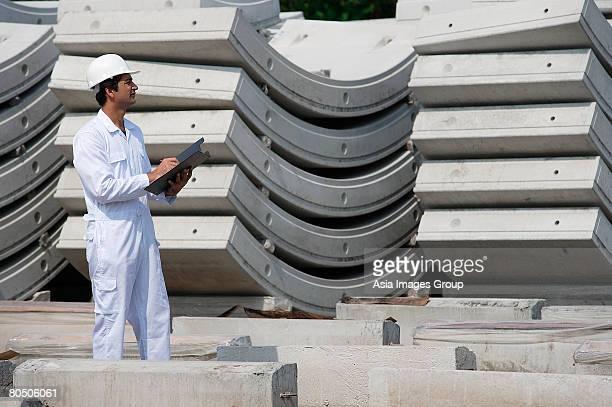 Man in work uniform writing on clipboard