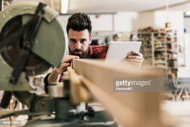 man in workshop with piece of wood and tablet - carpenter stock pictures, royalty-free photos & images