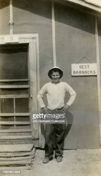 """Man in workwear stands outside of the """"Best Barracks"""" for a picture at Camp Flying Goose in Iowa, circa 1936."""