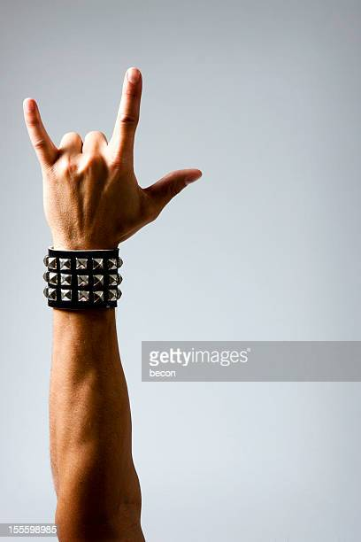 mann in armband, rock & roll hand-symbol - metallic look stock-fotos und bilder