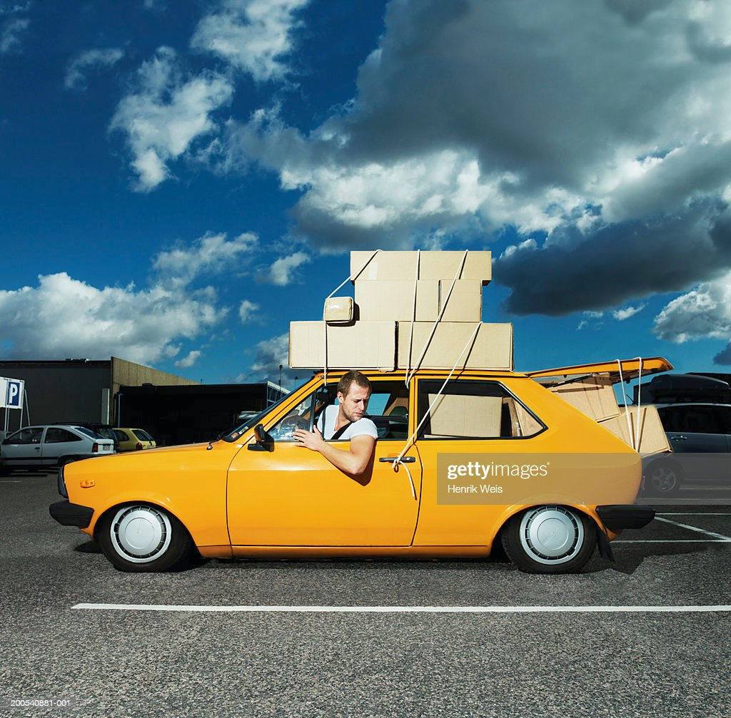 Man in yellow car filled with boxes and tied to roof : Stock Photo