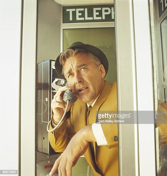 Man in yellow jacket talking on phone in telephone booth mid1960s