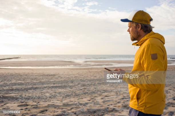 Man in yellow jacket, using smartphone on the beach