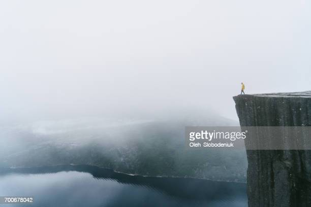 Man in yellow raincoat on the Preikestolen in fog in Norway