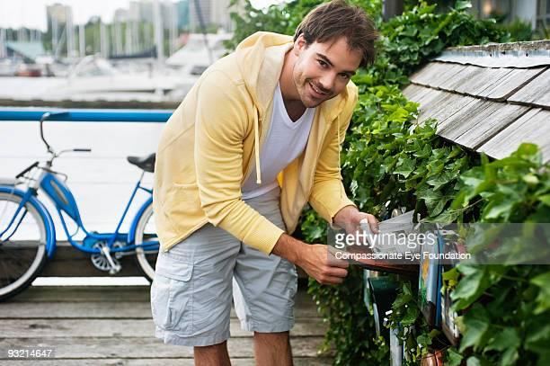 man in yellow sweater taking paper out of mailbox