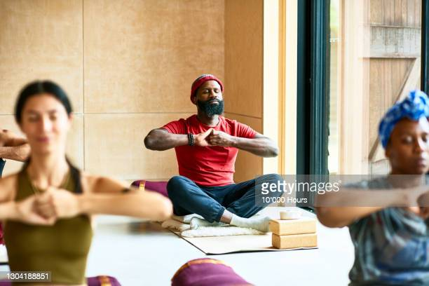 man in yoga pose with hands clasped - tranquility stock pictures, royalty-free photos & images
