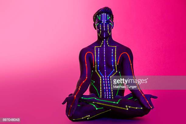 man in yoga pose with meridians painted on body - menschlicher körper stock-fotos und bilder