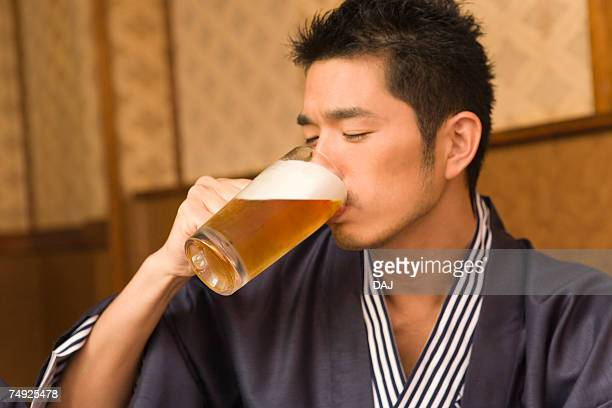 man in yukata drinking beer, side view, japan - beer stein stock photos and pictures