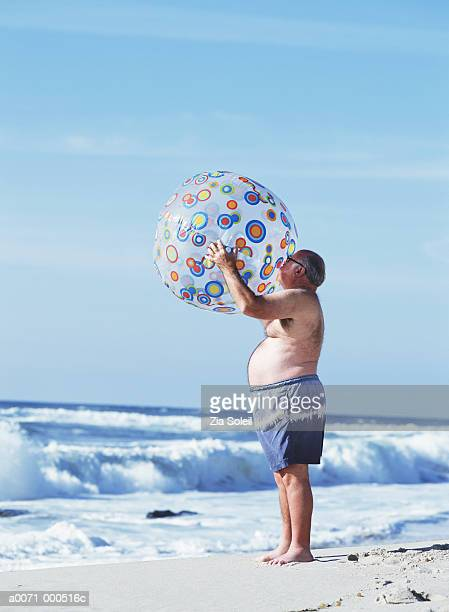 man inflating beach ball - man with big balls stock photos and pictures