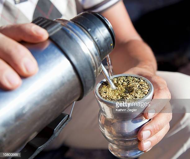 man infusing paraguay tea (mate) - paraguay foto e immagini stock