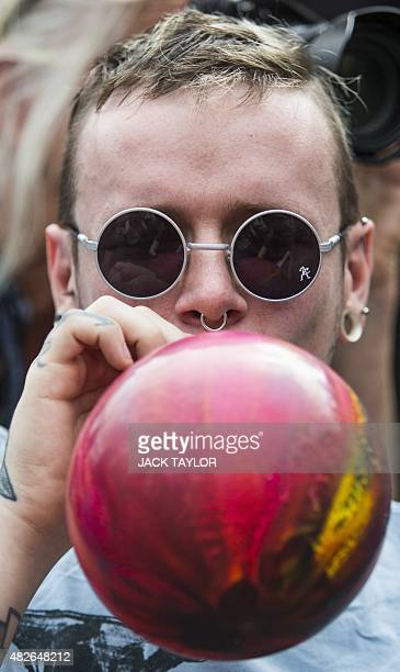 A man inhales Nitrous Oxide commonly known as laughing gas outside the Houses of Parliament in central London on August 1 2015 The group of...