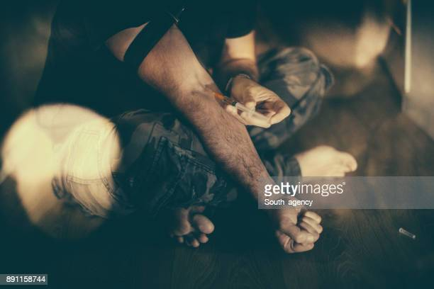 man injecting drug into arm - heroin addict arm stock photos and pictures