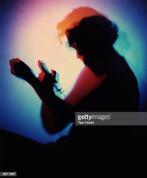man injecting himself, silhouette (multiple exposure, gel effect) - shooting up stock pictures, royalty-free photos & images