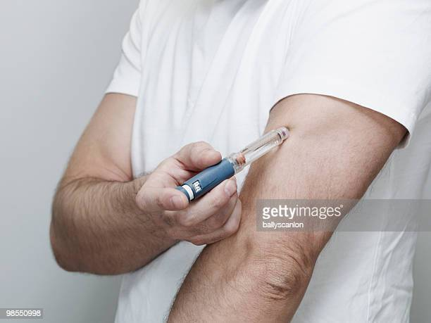 Man Injecting Himself with Insulin Pen in Arm.