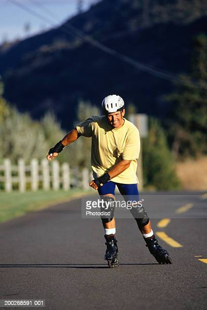man inline skating on open road - padding stock pictures, royalty-free photos & images