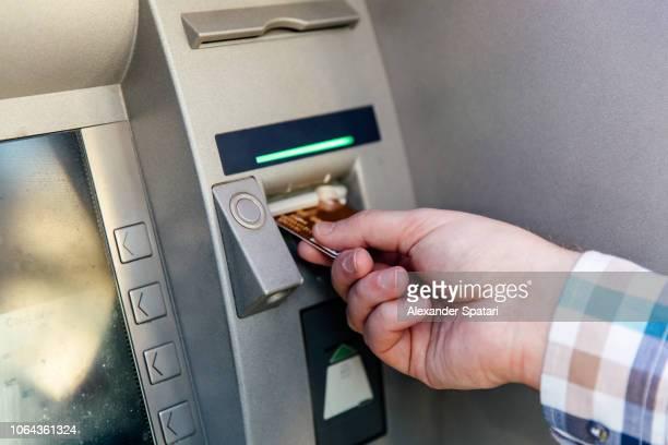 man inserting credit card in atm machine, close up - partie du corps humain photos et images de collection