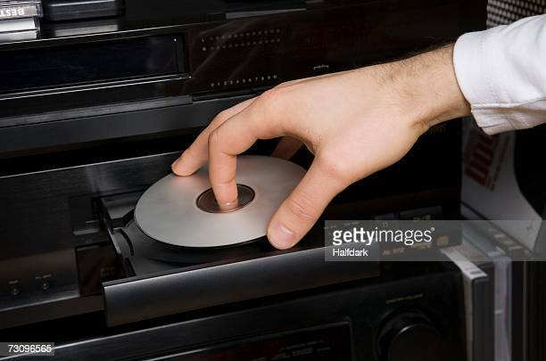 man inserting disk into dvd player - inserting stock pictures, royalty-free photos & images