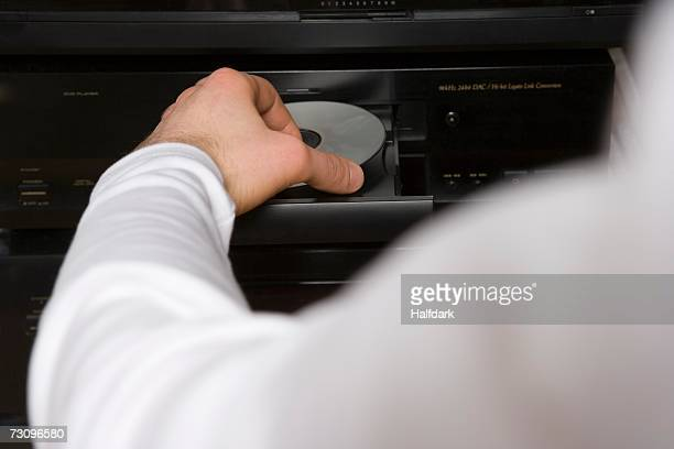 Man inserting disk into DVD player
