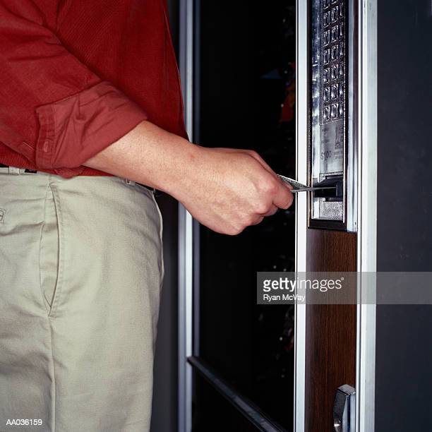 Man Inserting Paper Currency in a Vending Machine