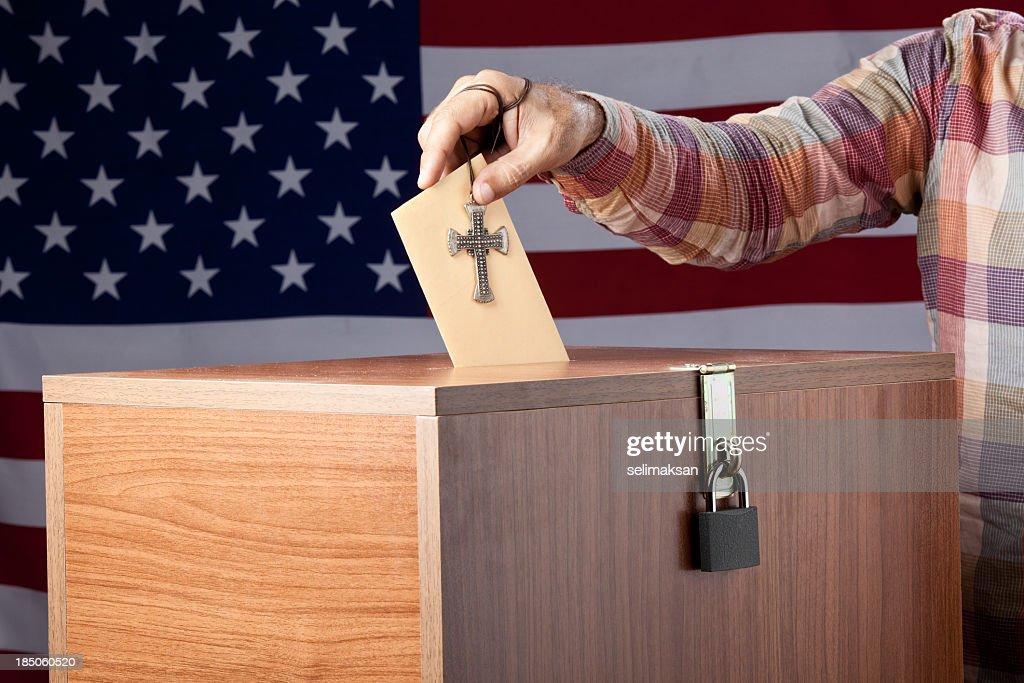 Man inserting poll envelope to ballot box before American Flag : Stock Photo