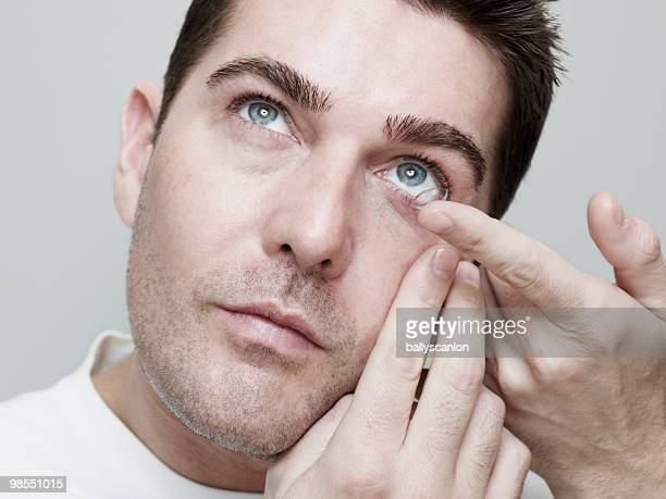 man inserting/guiding contact lenses. - contacts stock photos and pictures