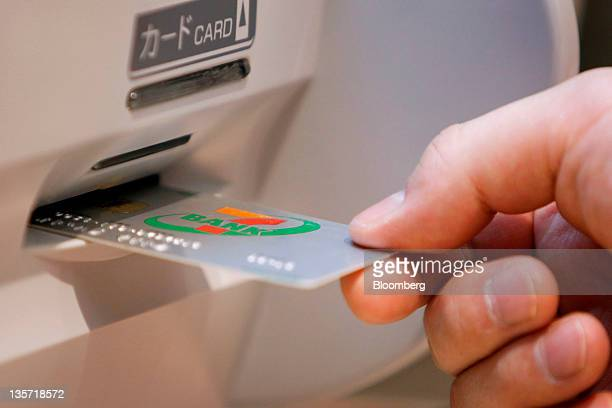 A man inserts a Seven Bank Ltd card into an automated teller machine at a branch in Tokyo Japan on Tuesday Dec 13 2011 Shareholders in Seven Bank Ltd...